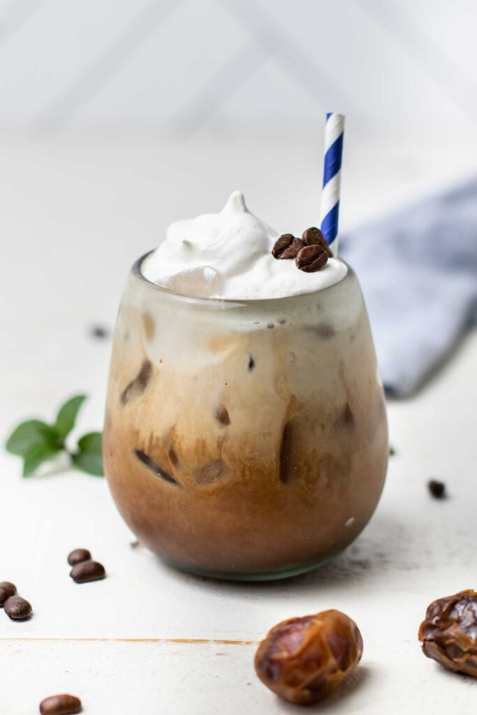 A iced mocha poured over ice and garnished with whipped cream.