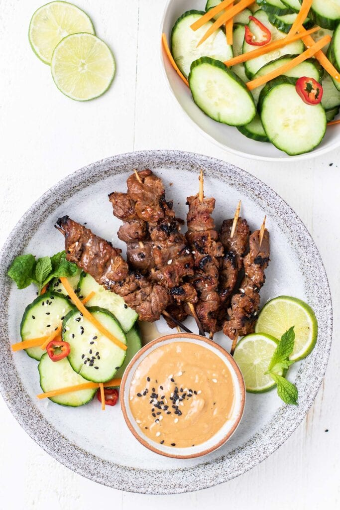 A plate with beef satay skewers, cucumber salad, and dipping sauce.
