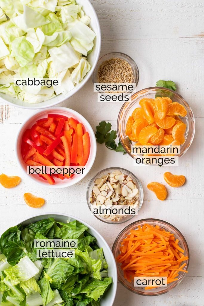 The ingredients for this cabbage salad shown chopped and in bowls, ready to combine.