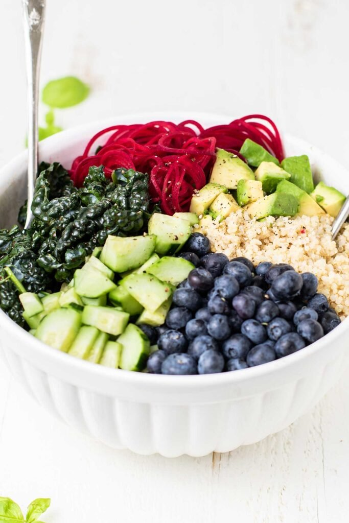 A bowl of kale topped with quinoa, beets, avocado, cucumber, and blueberries.