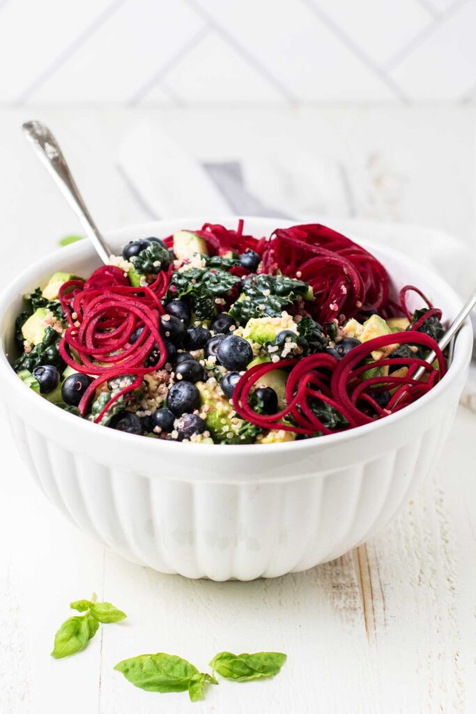 A vibrant kale salad with blueberries, quinoa and beets shown in a white salad bowl.