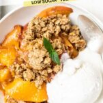 A close up look at a serving of peach crisp serve with ice cream.
