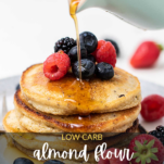 A stack of almond flour pancakes with maple syrup being drizzled on top.