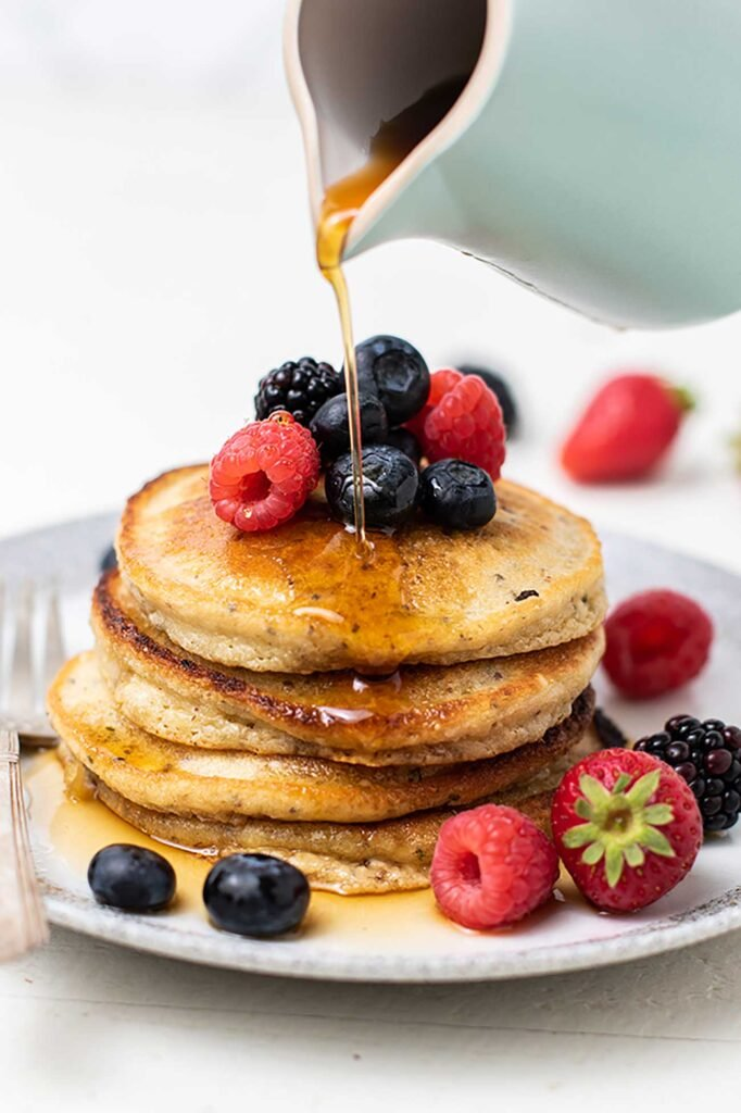 A stack of almond flour pancakes topped with berries, with maple syrup being poured on top.