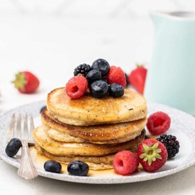A stack of 4 almond flour pancakes topped with strawberries, blueberries, blackberries and raspberries.