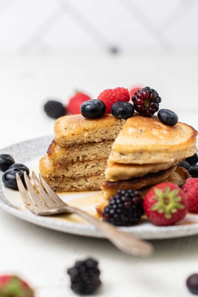 A stack of pancakes shown with a wedge cut out to show the light and fluffy interior.