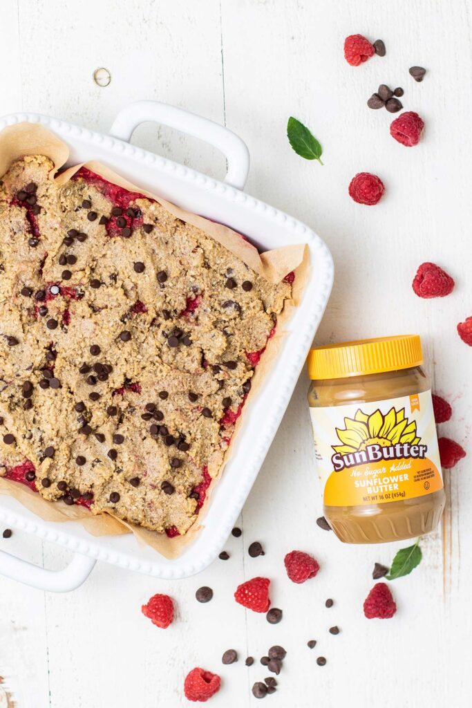 A jar of SunButter next to a pan of baked Raspberry Oatmeal Cookie Bars.
