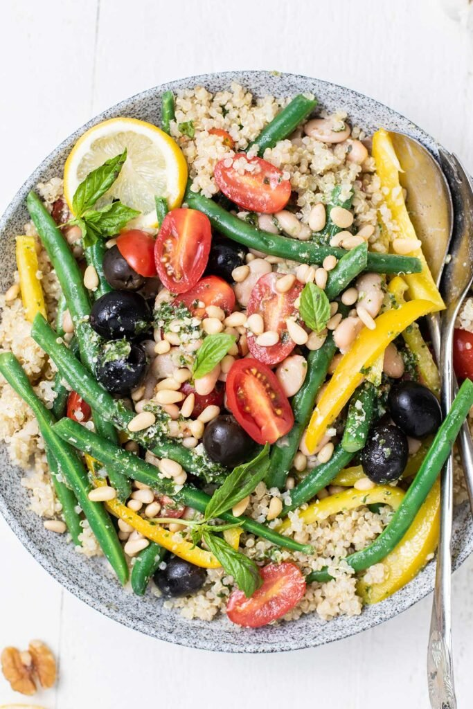 A close up look at a pesto quinoa salad loaded with green beans, tomatoes, olives, and peppers.
