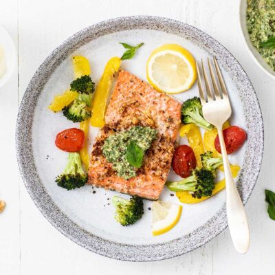 A plate with a piece of pesto salmon surrounded by colorful roasted veggies.