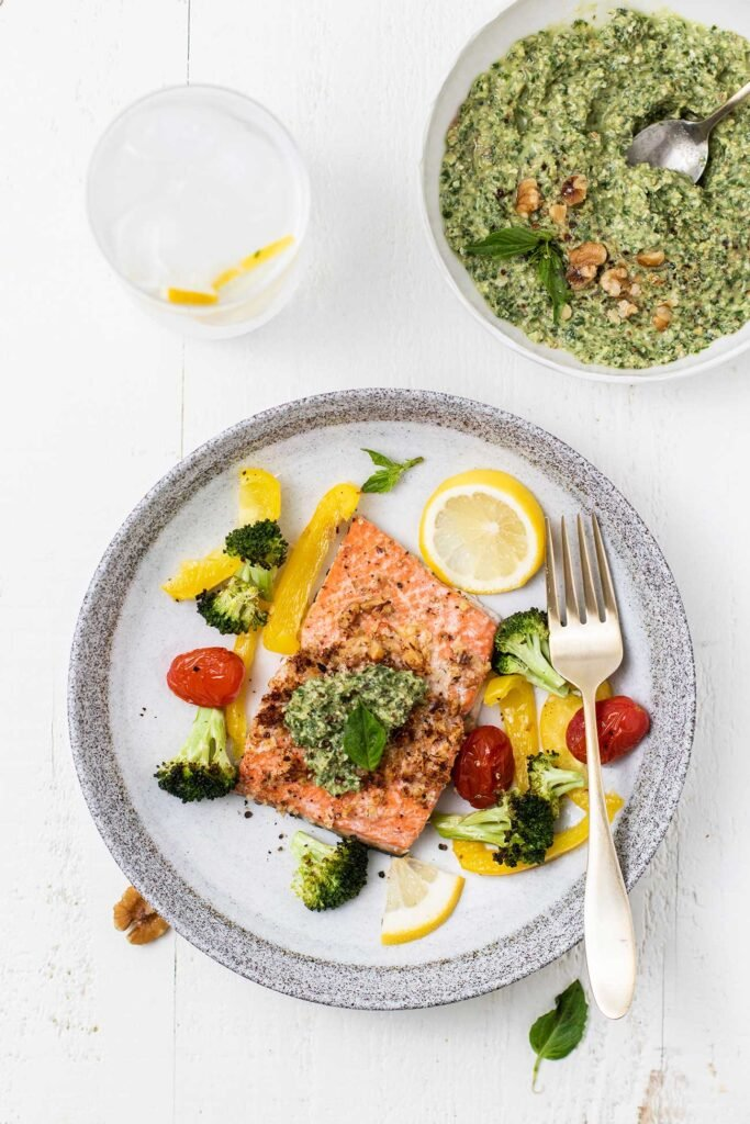 A plate with salmon and pesto served with veggies, next to a bowl of vibrant green pesto.