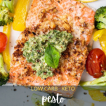 A close up look at a piece of salmon with a parmesan crust, topped with pesto.