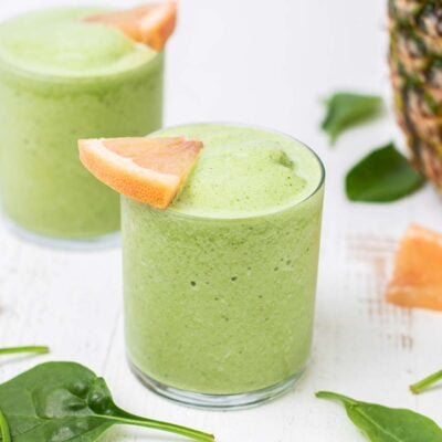 A vibrant green metabolism boosting smoothie shown garnished with grapefruit.