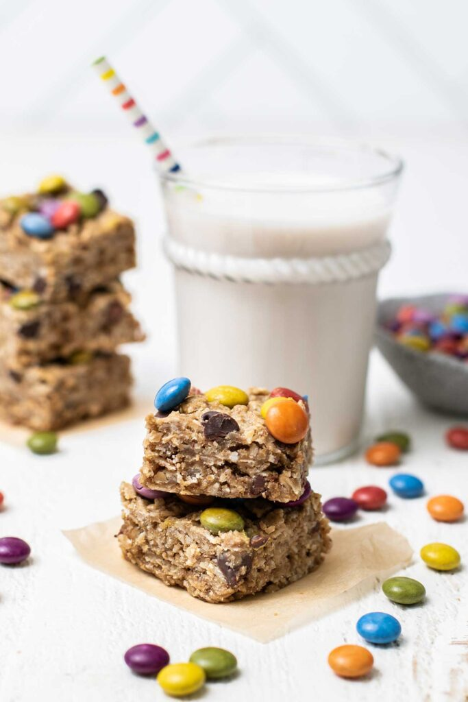 Stacks of cookies surrounding a glass of milk.