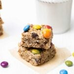 Two cookies stacked and shown surrounded by colorful candy pieces.