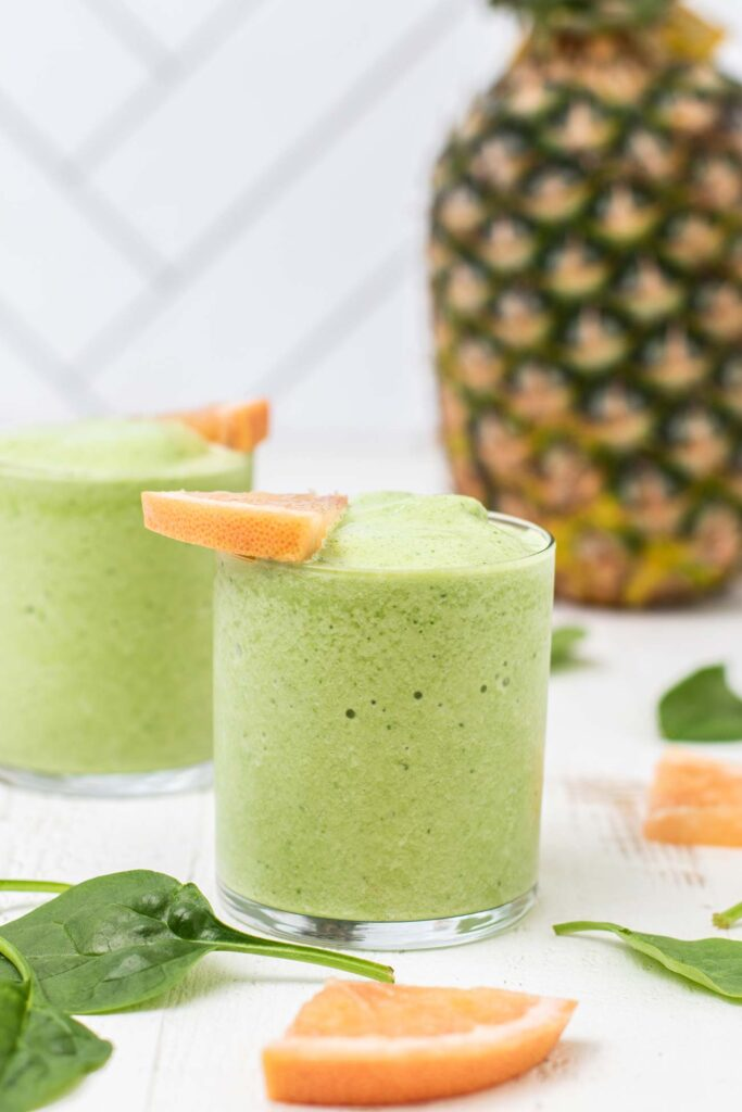 A vibrant green fat loss smoothie shown in front of a pineapple.